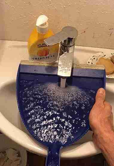 llenando cubeta con una pala en la lavamanos
